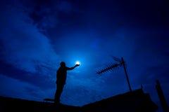 Obsługuje up na dachu, trzyma księżyc w pełni w ręce przeciw nocnemu niebu Obraz Royalty Free