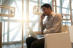 Obsługuje use laptop i mądrze telefon w lotniskowym holu Zdjęcia Royalty Free