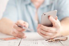 Obsługuje use mądrze telefon i trzymać kredytową kartę z robić zakupy online Online płatniczy pojęcie Fotografia Royalty Free