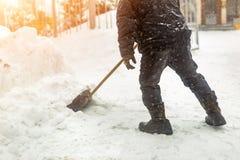 Obsługuje usuwać śnieg od chodniczka po ciężkiego opad śniegu Śnieżycy i miecielicy żniwo w zimie Śliski walkaway zdjęcia stock