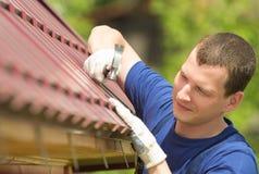 Obsługuje w błękitnym kostiumu naprawia dach dom, zakończenie obraz royalty free