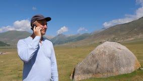 Obsługuje wezwanie telefon komórkowy podczas gdy halna wycieczka na zielonym średniogórze krajobrazie zdjęcie wideo