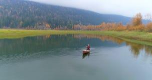 Obsługuje wiosłować łódź na jeziorze 4k zbiory