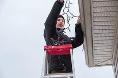 Obsługuje wiszących bożonarodzeniowe światła outdoors podczas gdy na drabinie Zdjęcie Stock