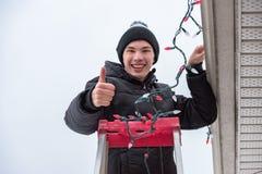 Obsługuje wiszących bożonarodzeniowe światła outdoors podczas gdy na drabinie Zdjęcie Royalty Free