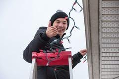 Obsługuje wspinać się drabinę wieszać bożonarodzeniowe światła outdoors Zdjęcia Stock