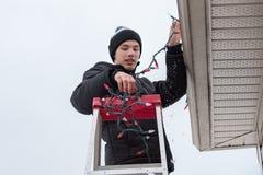Obsługuje wspinać się drabinę wieszać bożonarodzeniowe światła outdoors Zdjęcie Stock