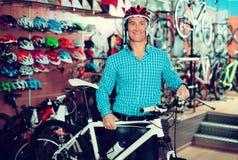 Obsługuje wybierać sporta hełm w sklepie i rower zdjęcie royalty free
