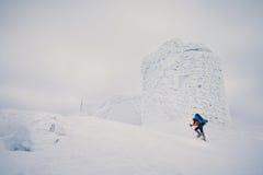 Obsługuje wycieczkować z plecakiem i karplami w zimy górze Fotografia Royalty Free