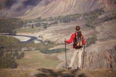 Obsługuje wycieczkowicza z trekking plecakiem na wierzchołku góra i słupami Zdjęcia Royalty Free