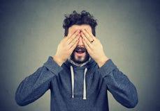 Obsługuje zakrywać jego oczy z rękami nad szarym tłem zdjęcia royalty free