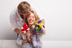 Obsługuje zaskakiwać jego kobiety z kwiatami i prezentem Zdjęcia Royalty Free