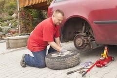 Obsługuje zmieniać przebijającą oponę na jego samochodowym rozluźnianiu przed jacking w górę pojazdu dokrętki z koła spanner Zdjęcie Royalty Free