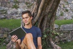 Obs?uguje czytelnicz? pastylk? i cieszy si? odpoczynek w parku pod drzewem zdjęcia stock