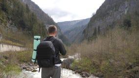 Obs?uguje turystycznego wycieczkowicza z plecakiem cieszy si? scenicznego widoku rzeki halnego krajobraz Podr?? wycieczkowicz pat zbiory