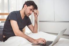Obs?uguje zaakcentowanego za pracie z laptopem w sypialni od Technologii i stylu ?ycia poj?cie Socjalny problem i zagadnienia opi zdjęcie stock