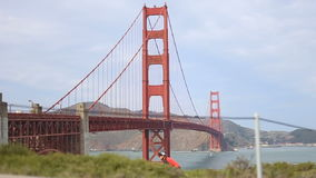 Obscured cyclists in San Fransicso with Golden Gate Bridge stock footage