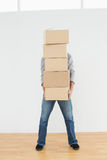 Obscured man carrying boxes in house Stock Photo