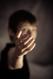 Obscured person with beckoning gesture. Obscured young male with extended arm in beckoning gesture over dark background stock photo