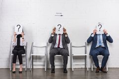 Obscured view of multicultural business people holding cards with question marks while waiting. For job interview stock photo
