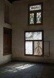 A obscuridade abandonada velha danificou a sala suja com as duas janelas ornamentado quebradas de madeira Imagem de Stock Royalty Free
