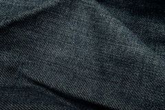 Obscuridade da dobra - fundo da textura de calças de ganga Imagem de Stock