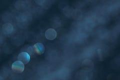 Obscuridade de Bokeh - o fundo azul com arco-íris borrado ilumina-se fotografia de stock royalty free