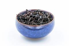 Obscuridade de Oolong do chinês - GUI vermelho de WuYi Rou do chá em uma bacia cerâmica azul Fotos de Stock Royalty Free