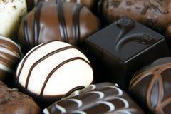 Obscuridade, leite e chocolates brancos fotos de stock
