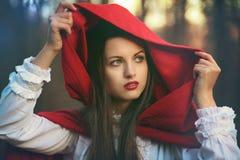 A obscuridade tonifica pouca capa de equitação vermelha Fotos de Stock Royalty Free