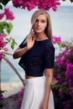 Obscuridade vestindo da mulher caucasiano loura - parte superior do laço e saia azuis do branco Levantamento entre flores cor-de- fotografia de stock