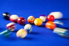 Obscuro e mover-se de bolas de bilhar em uma mesa de bilhar Fotografia de Stock Royalty Free