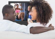 Observação de sorriso dos pares esportes na televisão imagens de stock