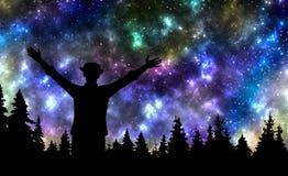A observação do homem protagoniza no céu noturno acima da floresta do pinho imagem de stock