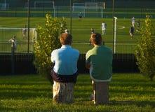 Observação do pai e do filho mais nova seu jogo Imagens de Stock Royalty Free