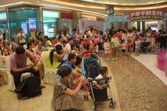 Observación de la demostración de los niños de padres en el SHENZHEN Tai Koo Shing Commercial Center Imagen de archivo libre de regalías