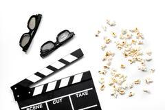 Observación de la película Clapperboard, gafas de sol y palomitas de la película en la opinión superior del fondo blanco Fotos de archivo