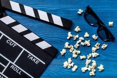 Observación de la película Clapperboard, gafas de sol y palomitas de la película en la opinión superior del fondo de madera azul  Foto de archivo