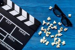 Observación de la película Clapperboard, gafas de sol y palomitas de la película en la opinión superior del fondo de madera azul  Imagen de archivo libre de regalías