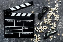Observación de la película Clapperboard, gafas de sol y palomitas de la película en la opinión superior del fondo de piedra gris  Imagenes de archivo