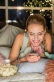 Observación femenina sonriente en el teléfono móvil Fotografía de archivo libre de regalías