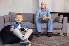Observant attentive man watching his grandson playing. Both inspired. Adorable caring engaged grandpa sitting on a couch and observing the mastery of his Royalty Free Stock Images