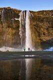 Observant dans la crainte, arc-en-ciel dans le jet outre de la cascade de Seljalandsfoss, Islande Photos libres de droits