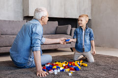 Observant helping kid finding a missing piece. I got it. Brilliant amusing hilarious men sitting on the floor and starting building something while using a royalty free stock images