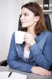 Observant young businesswoman drinking coffee Royalty Free Stock Photos