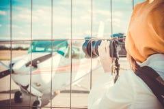 Observateur photographiant le petit avion par la barrière de l'aéroport Photographie stock libre de droits
