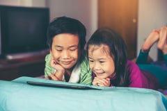 Observation asiatique d'enfants visuelle et jouer le jeu sur le comprimé numérique photos libres de droits
