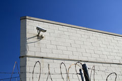 Observation camera. On the warehouse wall behind a fence with barbwire stock images