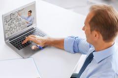 Observation d'homme d'affaires webinar sur l'ordinateur portable au bureau image libre de droits