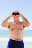Observation d'oiseau d'homme aîné à la plage Images libres de droits